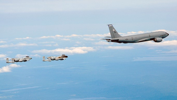 Image of KC-135 air refueling tanker flying with two A-10 fighter airplanes flying behind.